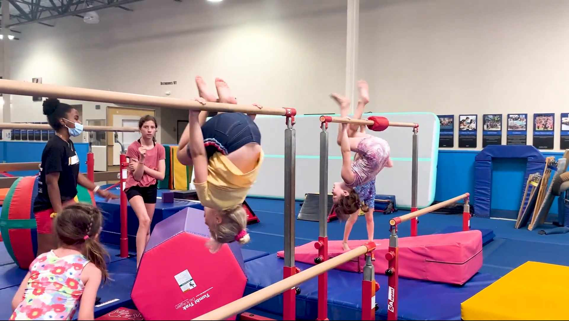 Children hanging upside down on small uneven bars