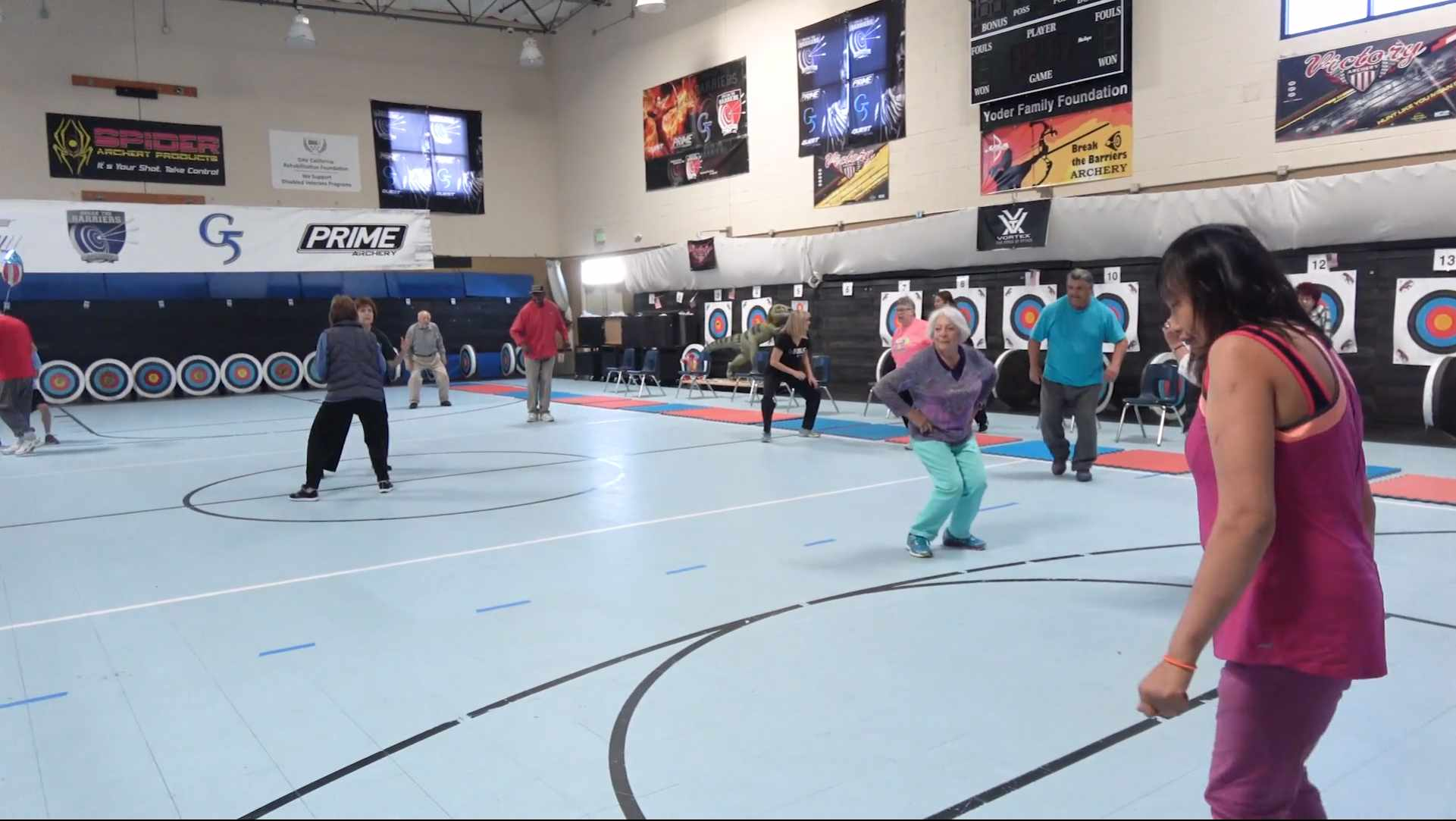 Group of people doing squat exercises across a light blue basketball court